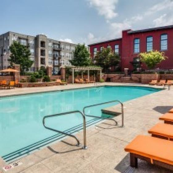 Image of Alpha Mill swimming pool, poolside lounge chairs, cabanas, red brick fence and apartment building exteriors