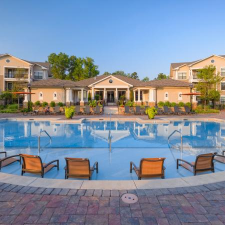 View of Pool Area, Showing Loungers, Fenced-In Area, and Adjacent Resident Clubhouse at Heights at Meridian Apartments