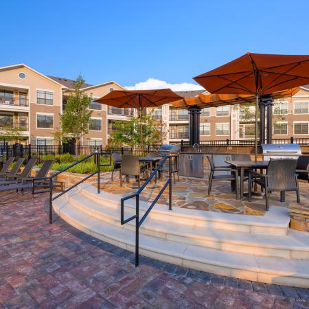 View of Grilling Lounge, Showing Fenced-In Area, Picnic Areas, and Loungers at Heights at Meridian Apartments