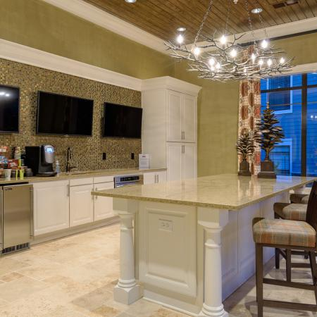 View of Resident Clubhouse, Showing Community Kitchen with Island, Coffee Bar, and TVs at Heights at Meridian Apartments