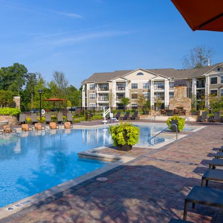 View of Pool Area, Showing Fenced-In Area, Loungers, and Outdoor Furniture at Heights at Meridian Apartments