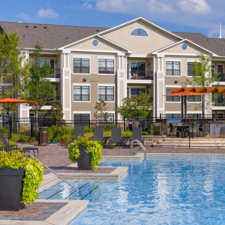 View of Pool Area, Showing Loungers, Umbrellas, and Grilling Lounge at Heights at Meridian Apartments