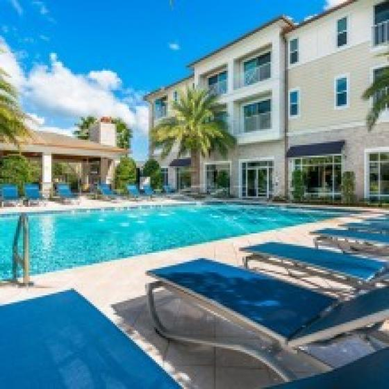 The Marq Highland Park, exterior, sparkling blue swimming pool, white building, 3 levels, blue lounge chairs, palm trees