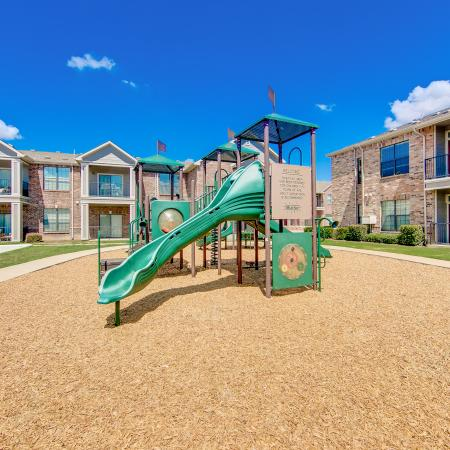 View of Playground, Showing Building Exteriors and Adjacent Sand Volleyball Court at Enclave on Golden Triangle Apartments