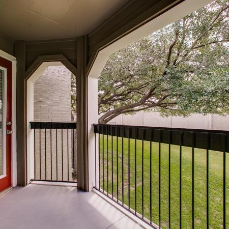 View of Patio, Showing Railing, Grass, and Door to Living Room at The Arbors of Las Colinas Apartments