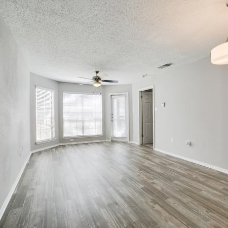 View of Living Room, Showing Plank Wood Flooring, Ceiling Fan, and Window View at The Arbors of Las Colinas Apartments