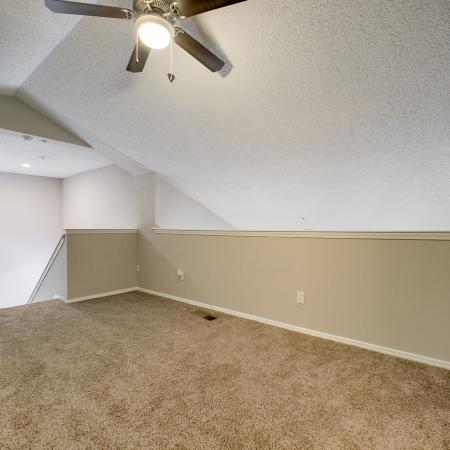 View of Bedroom, Showing Ceiling Fan, Vaulted Ceiling, and Staircase at The Arbors of Las Colinas Apartments