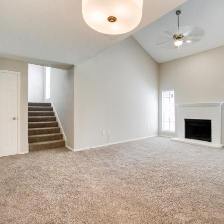 View of Living Room, Showing Fireplace, Ceiling Fan, and Window View at The Arbors of Las Colinas Apartments
