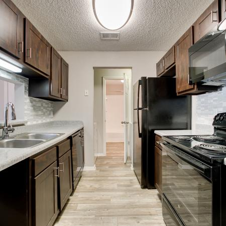 View of Kitchen, Showing Plank Wood Flooring, Breakfast Bar, and Gas Appliances at The Arbors of Las Colinas Apartments