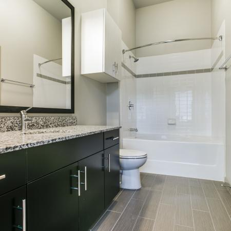 View of Bathroom, Showing Granite Counter Top, Single Vanity, and Garden Tub at Routh Street Flats Apartments