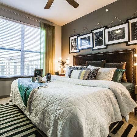 View of Bedroom, Showing Layered Bedding, Ceiling Fans, and Window Views at Routh Street Flats Apartments