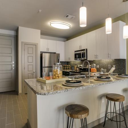 View of Kitchen, Showing Stainless Steel Appliances, Bar Stools, and Pantry at Routh Street Flats Apartments