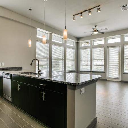 View of Kitchen, Showing Plank Porcelain Floors and View of Living Room at Routh Street Flats Apartments