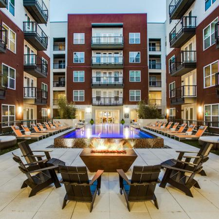 View of Pool Area, Showing Fire Pit, Chairs, Loungers, Patios, and Balconies at Routh Street Flats Apartments