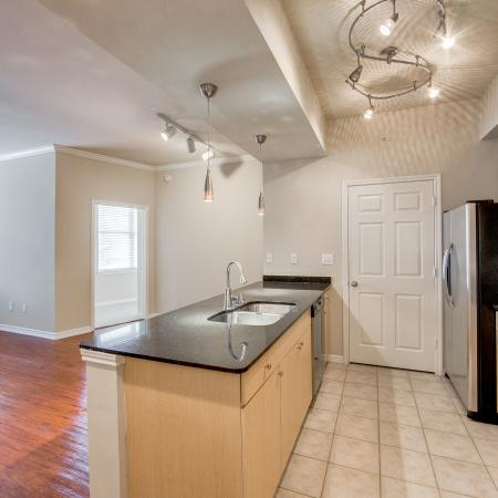 View of Classic Apartment Interior, Showing Kitchen with Stainless Steel Appliances and View of Living Room at McKinney Uptown Apartments
