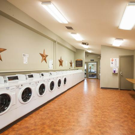 View of Clothing Care Center, Showing Washers, Dryers, and Folding Area at Fox Point in Old Farm Apartments