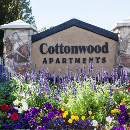 View of Entrance Sign, Showing Name of Community and Flower Beds at Cottonwood Apartments