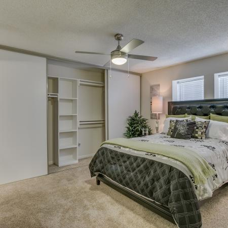 View of Bedroom, Showing Layered Bedding and Ceiling Fan at The Regatta Apartments