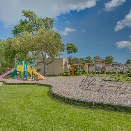 View of Playground, Showing Swing Set, Slides, and Picnic Table at The Regatta Apartments