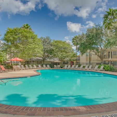 View of Pool Area, Showing Fenced-In Area, Picnic Area, and Loungers at The Regatta Apartments