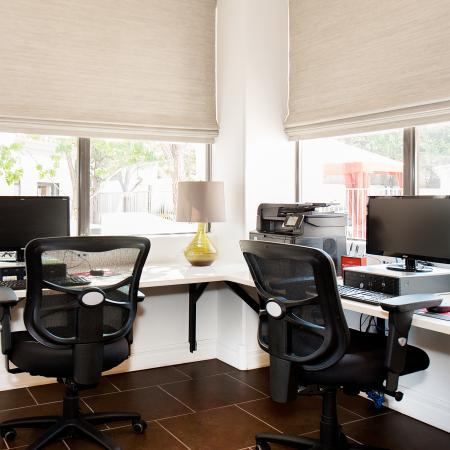 View of Business Center, Showing Desk, Two Flat Screen Monitors, Printer, and Windows at Pavilions Apartments