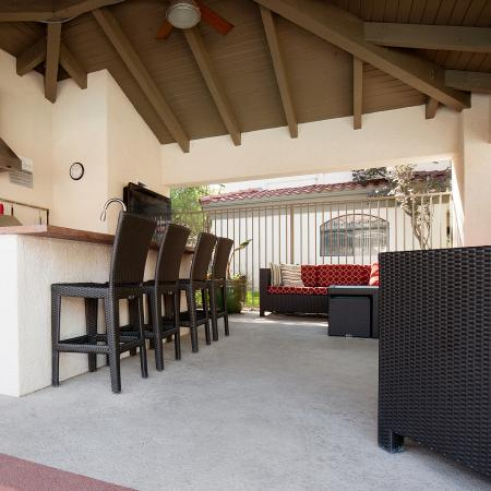 View of Outdoor Lounge, Showing Seating, Kitchen, Bar Top With Chairs, and Ceiling Fan at Pavilions Apartments