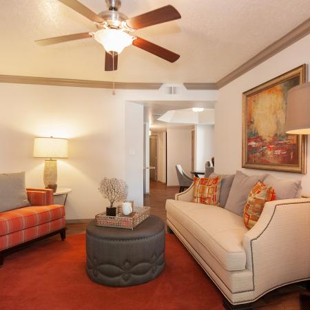 View of Furnished Living Room, Showing Ceiling Fan and View Leading to Dining Room at Pavilions Apartments