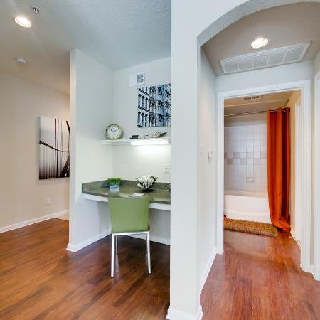 View of Upgraded Apartment Interior, Showing Living Room with Built-In Desk, and View of Bedroom and Bathroom at Stonebriar of Frisco Apartments
