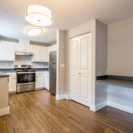 View of Renovated Apartment Interior, Showing Kitchen with Plank Flooring and Stainless Steel Appliances at Scott Mountain Apartments