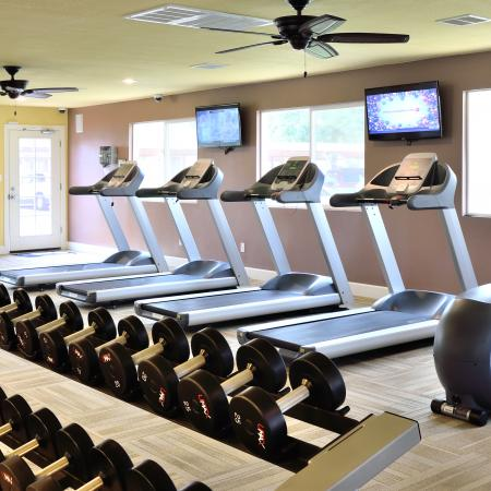 View of Fitness Center, Showing Cardio Equipment, Ceiling Fans, Flat Screen TV's and Weight Bench at Camelot Apartments