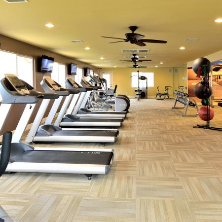 View of Fitness Center, Showing Cardio Equpment, Ceiling Fans, Flat Screen TV's and Weight Bench at Camelot Apartments