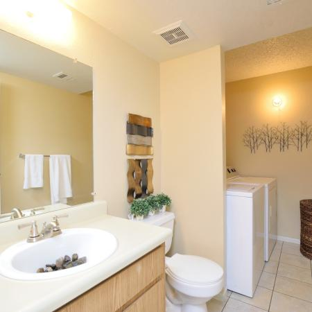 View of Furnished Bathroom, Showing Single Vanity, Washer, and Dryer at Camelot Apartments