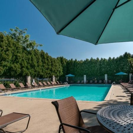 View of Resort-Style Pool, Showing Loungers, Table With Chairs and Umbrella at Clearview Apartments