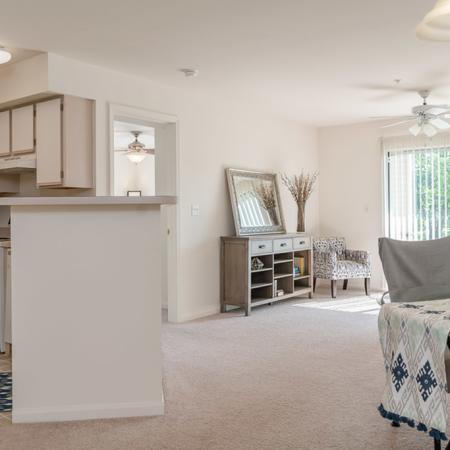 View of Furnished Living Room, Showing Bar Top, Dining Area, Carpet, Sliding Glass Door and Décor at Clearview Apartments