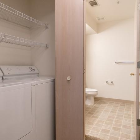 View of Attached Laundry Room, Showing Full Size Washer and Dryer, and Shelving at Clearview Apartments