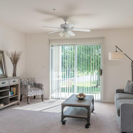 View of Furnished Living Room, Showing Couch, Carpet, Ceiling Fan, Sliding Glass Door and Décor at Clearview Apartments