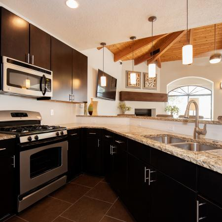 View of Community Kitchen, Showing Bar Top With Chairs, Stainless Steel Appliances, and Double Sink at Pavilions Apartments
