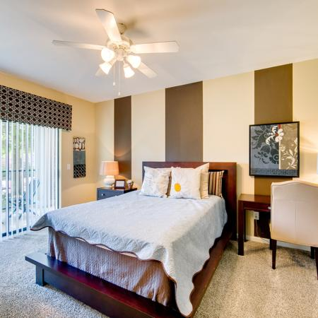 View of Furnished Bedroom, Showing Carpet, Ceiling Fan, and Sliding Glass Door to Patio at Enclave on Golden Triangle Apartments