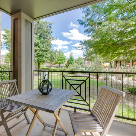 View of Private Patio, Showing Table and Chairs, Landscaping, and Community View at Enclave on Golden Triangle Apartments
