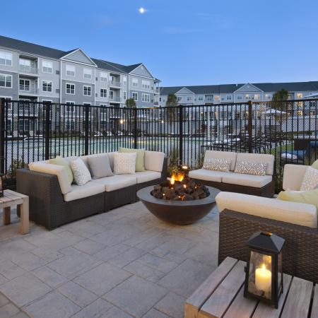 View of Pool Area, Showing Outdoor Couches, Firepit, Fenced-In Pool, and Apartment Buildings in Background at Parc Westborough Apartments