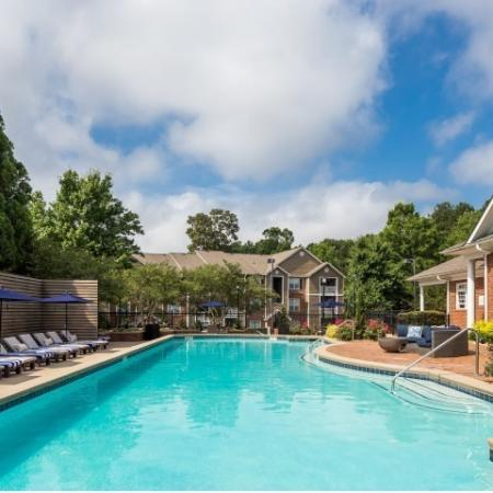 Image of Retreat at Peachtree City's swimming pool with poolside loungers and apartment building in the background
