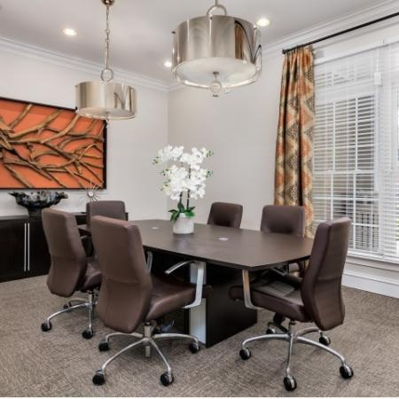 Image of resident business center with a conference table, chair and decorative flowers