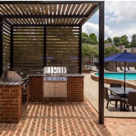 Image of grilling area with 2 grills and picnic table and chairs at Retreat at Peachtree City