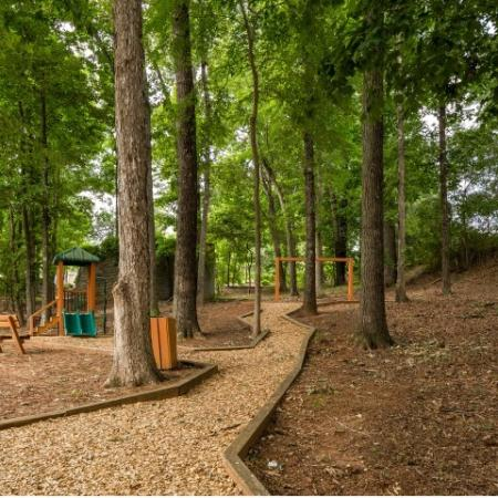 Image of walking trail at Retreat at Peachtree City in a wooded area and a children's playground and bench