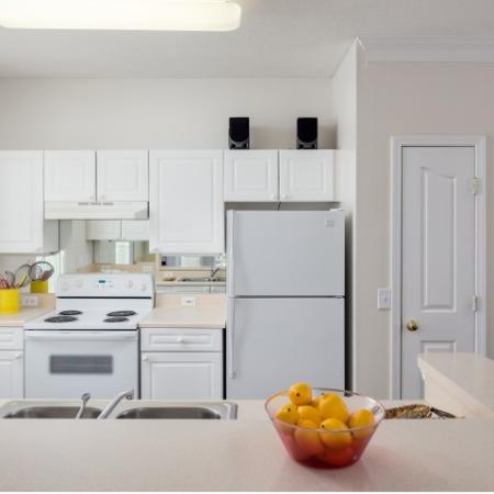 Image of apartment kitchen at Retreat at Peachtree City with white appliances and breakfast bar