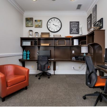 Image of resident business center with desk, 2 desktop computers and a red lounge chair