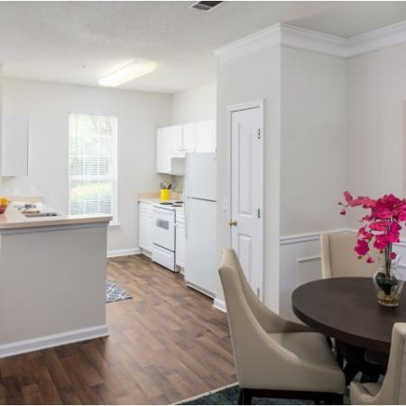 Image of apartment kitchen and dining room with dining table, chairs and wood-plank vinyl flooring