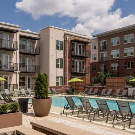 View of Pool Area, Showing Loungers, Fenced-In Area, and Apartment Buildings in Background at The Melrose Apartments
