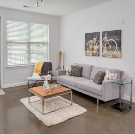 View of Living Room, Showing Stained Concrete Flooring, Couch, and View of Window at The Melrose Apartments