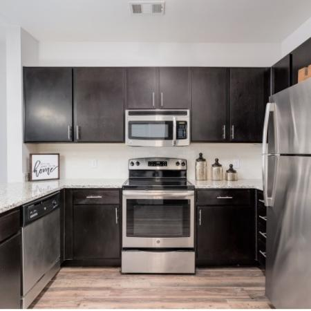 View of Kitchen, Showing Plank Wood Flooring, Granite Countertop, and Stainless Steel Appliances at The Melrose Apartments